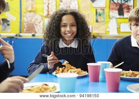Schoolchildren Sitting At Table Eating Cooked Lunch