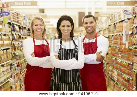 Supermarket Workers Standing In Grocery Aisle