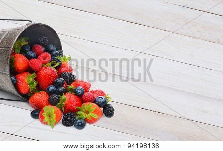 A pail laying on its side with assorted berries spilling on to a rustic white wood table. Horizontal format with copy space.