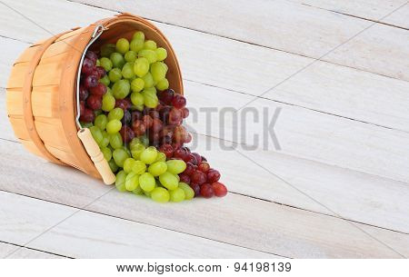 A basket of grapes laying on its side, with fruit spilling onto a rustic white table. Horizontal format with copy space.
