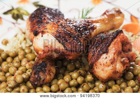 Roasted chicken legs with rice and green peas, classic of traditional cuisine