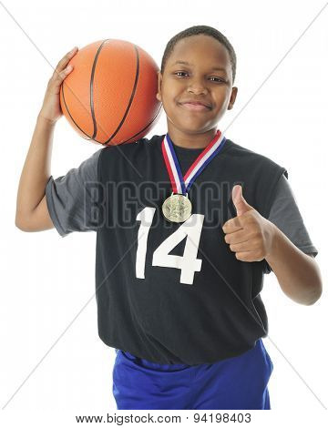A happy preteen athlete supporting his basketball on his shoulder, a thumbs up with the other hand and a red, white and blue winning ribbon and metal around his neck.  On a white background.
