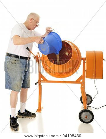 A senior adult man pouring sand into his cement mixer.  On a white background.
