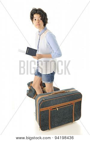 A pretty young teen looking back cautiously as she stand with her passport and boarding pass in her hand and luggage by her side. On a white background.