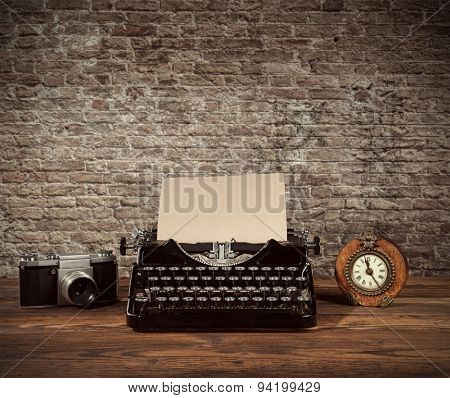Retro typewriter, alarm-clock and camera placed on wooden planks. Old brick wall as background with copyspace.