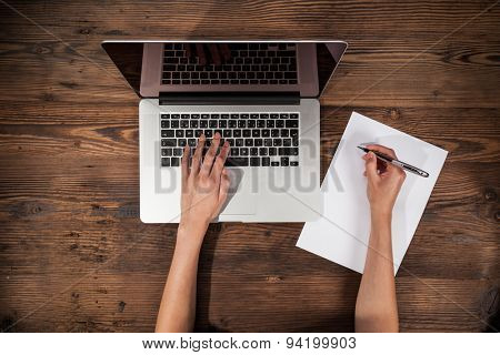 Aerial view of woman typing on laptop. Placed on wooden desk