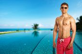 foto of infinity pool  - Man at swimming pool in the tropical hotel - JPG