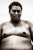 stock photo of body fat  - Fat naked upper body and belly stomach of an African tribal man showing proud expression on his face in white isolated background in heavy grain grunge style - JPG