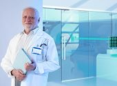 stock photo of professor  - Old white haired professor doctor standing in front of MRI room at hospital - JPG