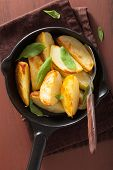 picture of baked potato  - baked potato wedges in black frying pan - JPG