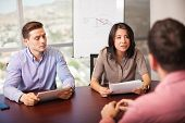 image of pov  - Couple of Latin people with resume in hand interviewing a job candidate in a meeting room