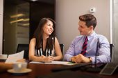 stock photo of flirt  - Beautiful brunette flirting and smiling with one of her colleagues in the middle of a meeting - JPG