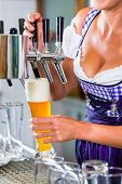 image of drawing beer  - Innkeeper in Bavarian pub drawing beer - JPG