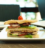 stock photo of tomato sandwich  - Bacon Sandwich on white plate with small tomato on top - JPG