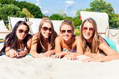 picture of sun-tanned  - Four woman lying on beach sand - JPG