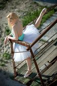 image of tutu  - Soft ballerina with blond hair in a white tutu standing on old rusty stairs - JPG