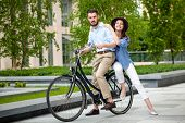 stock photo of opposites  - Young couple sitting on a bicycle opposite the green city park  - JPG