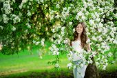 pic of allergy  - Young spring fashion woman in spring garden Springtime Summertime Trendy girl in the flowering trees in then at sunset in spring  summer landscape background Allergic to pollen of flowers Allergy  - JPG