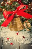 picture of christmas bells  - Christmas composition with golden bell with red satin ribbon bow and branch of christmas tree - JPG