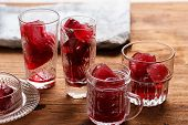 foto of sorrel  - Preparation of frozen hibiscus tea also known as karkade agua fresca or red sorrel on a wooden table - JPG