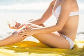 stock photo of sun-tanned  - Close up view of Pretty blonde woman putting sun tan lotion on her leg at the beach - JPG