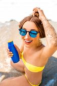 pic of suntanning  - Woman showing suntan cream bottle on the beach - JPG