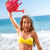 image of emotional  - Emotional woman pouring water from watering can on the beach - JPG