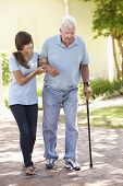 picture of grandfather  - Teenage Granddaughter Helping Grandfather Out On Walk - JPG