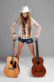 image of cowgirls  - Sesy cowgirl in cowboy hat with a nylon string acoustic guitar - JPG