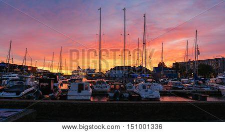 Tallinn Estonia - October 2 2016: Dramatic sunrise over port of Tallinn. Modern marina for recreational vessels in the very heart of city.