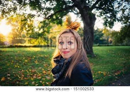 Emotional young woman with bunch of leaves make a grimace in autumnal park. Fall season concept