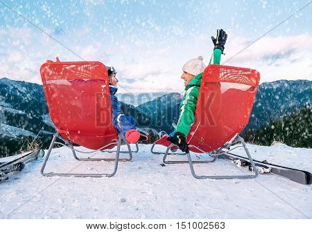 Two skiers relax in chiars on the mountain top