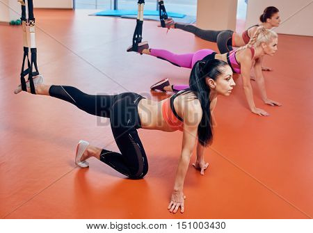 Beautiful young women with long straight brunet hair is doing exercises with TRX