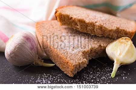 The garlic and rye bread salted. A close up a kitchen towel on a background a dark table with spilled salt