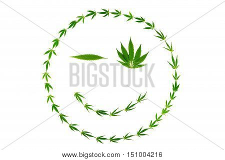 Winking smiling face made of cannabis leaves isolated on white background