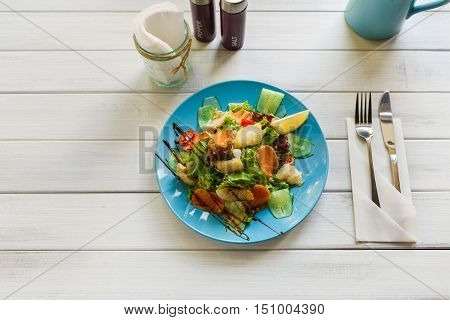 Restaurant healthy food, seafood salad top view with copy space on white wood. Salmon and cod fish salad with vegetables and lettuce on blue plate. Appetizing dish served with sauce, dinner meal.