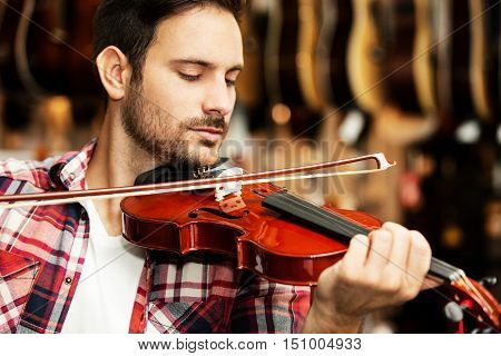 Young man is playing violin in musical instruments store.