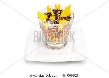 Glass of fresh exotic fruit exotic salad on white background