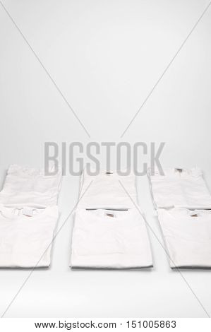 Folded white shirts in neat stacks with neutral bright background with copy space