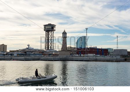 BARCELONA, SPAIN - SEPTEMBER 15. Man on inflatable boat in front of the shipyards of Port Vell in Barcelona on September 15, 2016. In the back the new landmark W-Barcelona Hotel
