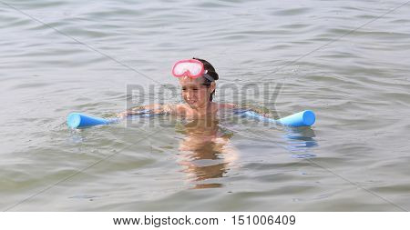 Little Girl Plays With The Floating Plastic Tube And Diving Mask