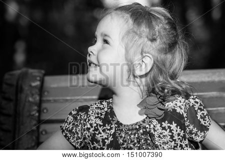 An adorable little girl looking to the light in front of a black background. Black and white.