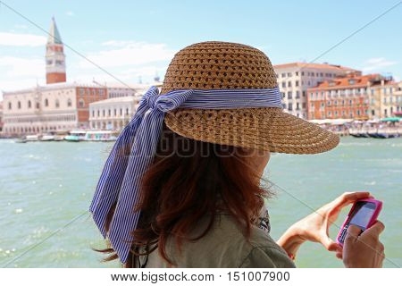 Young Woman Uses The Smartphone To Send A Picture In Venice Ital