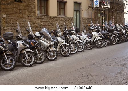 Florence Italy - 4 September 2016: A row of parked motorbikes on the street. Compact kinds of transport are very popular in Florence due to narrow streets.