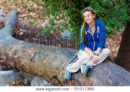 Jolly cute smiling Girl sportive and hippie Style Clothing and dreadlocks hairstyle sitting on fallen Tree in Wild Spring Forest outdoors