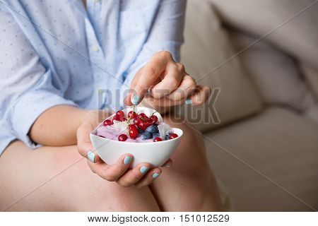 Closeup of woman's hands holding cup with organic yogurt with blueberries coconut and fresh mint. Homemade vanilla yogurt in girl's hands. Breakfast snack. Healthy eating and lifestyle concept