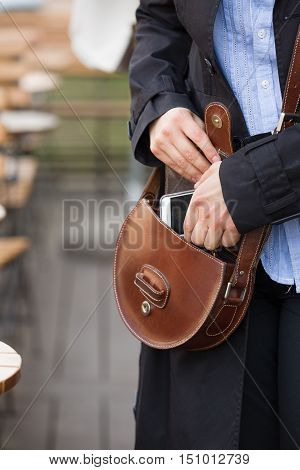 Closeup of woman's hands putting smartphone into brown leather purse. Girl with bag and telephone on the lunch break. Outdoors.