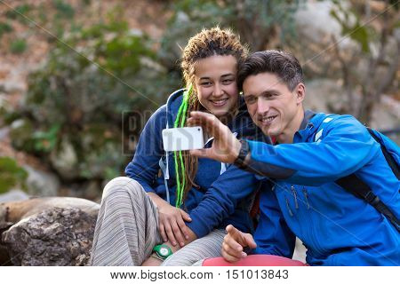 Two Hikers Handsome Man Cute Girl with Dreadlocks Hair Style smiling taking self Portrait with Camera of smart phone on Hike in Spring Time Forest