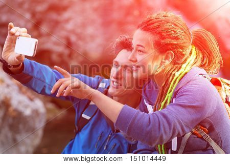 Young Family Handsome Man and Cute Woman with Hippie Hair Style taking self Portrait Photo with Camera phone on Hike in Spring Time Forest