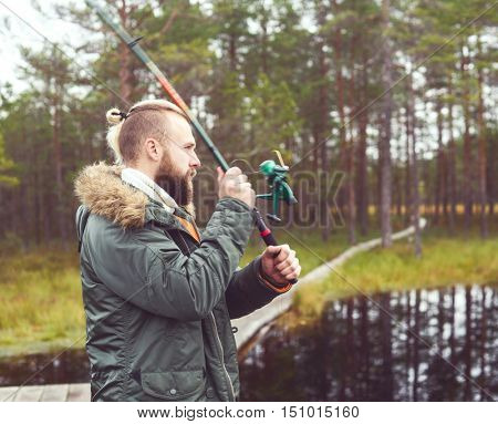 Hipster fisherman with a spinning rod catching fish on a river or lake. Man on a weekend. Hobby, leisure and active summer and autumn concept. Rural background. Color filter.